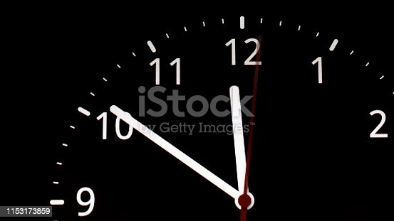 istock analog clock. clock about to 12 midnight or midday, conceptual of New Year and countdown. isolated on black background 1153173859