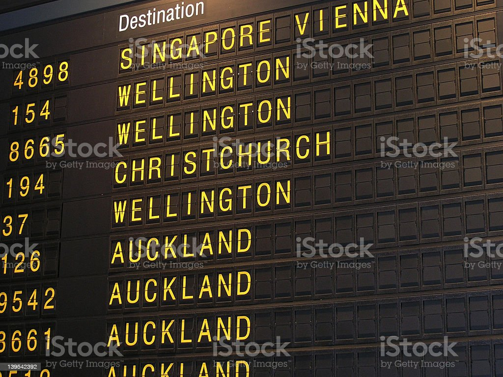A analog departures board at an airport stock photo