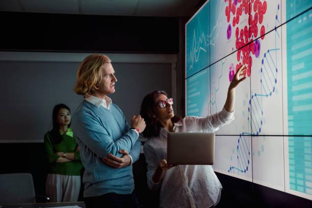 analysing data on a large display screen - scoprire nuovi terreni foto e immagini stock