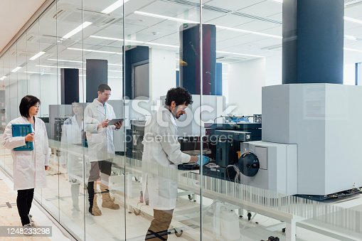 A female scientist walks down a corridor and observes her colleagues. Two scientists can be seen working with large machinery through a clear glass wall in a laboratory.