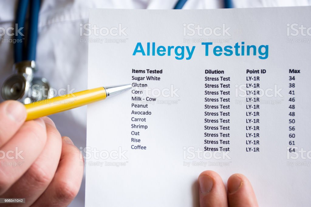 Analysis and testing for allergies photo concept. Doctor points with pen in his hand on result of patient allergy test in foreground, standing in medical gown with stethoscope in blurred background stock photo