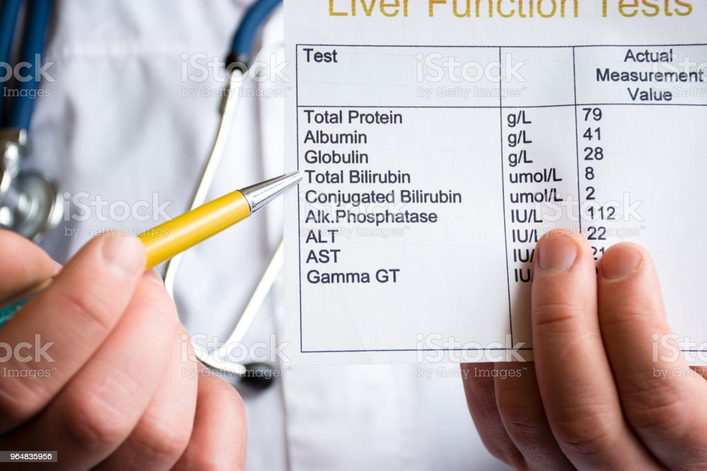 Analysis of bilirubin concept photo. Doctor holding laboratory test of liver function and indicates ballpoint pen on rate of total bilirubin. Raising or lowering level as indicator of liver disease royalty-free stock photo