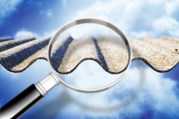 Analysis of the compounds of a dangerous asbestos roof - concept image with magnifying glass - foto stock