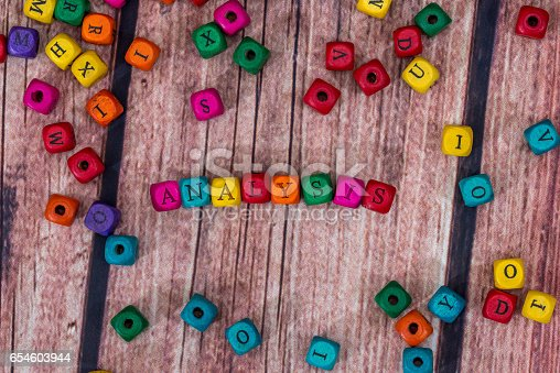 istock analysis - word created with colored wooden cubes on desk. 654603944
