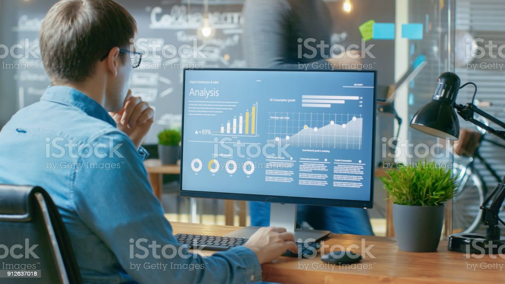 Analyst Works on a Personal Computer Showing Statistics, Graphs and Charts. In the Background His Coworker and Creative Office. - Foto stock royalty-free di Affari