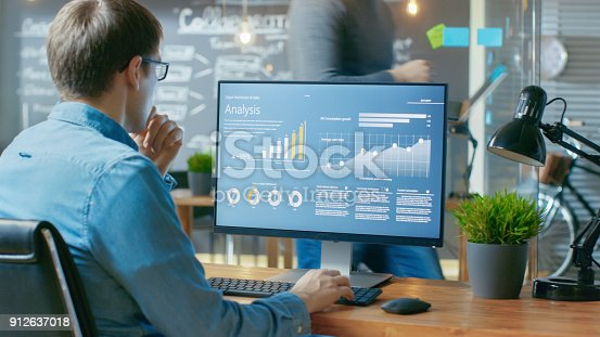 istock Analyst Works on a Personal Computer Showing Statistics, Graphs and Charts. In the Background His Coworker and Creative Office. 912637018