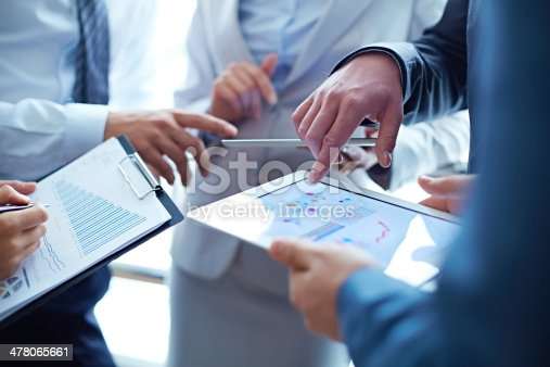 Unrecognizable business people examining financial reports and analyzing business growth