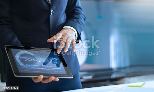 istock Analyzing data, Businessman working and checking market data in office, hand pointing on the data presented in the chart on tablet 865596974