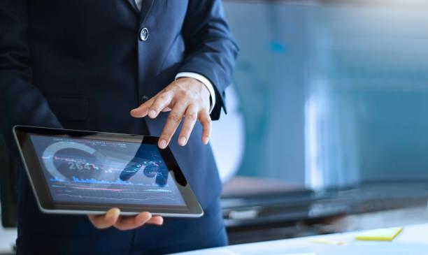 タブレット上のグラフに表示されるデータを指す手の分析データ、ビジネスマン、オフィスでは、市場データをチェック - タブレット端末 ストックフォトと画像