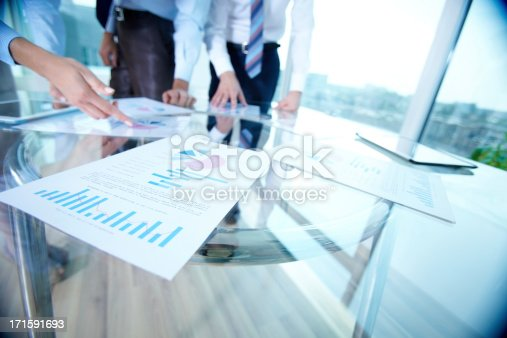 Image of spreadsheets on glass table during discussion of strategy