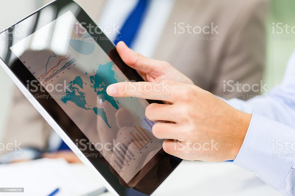 Analyzing financial reports on digital tablet royalty-free stock photo