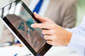 Businessman analyzing financial reports on digital tablet.