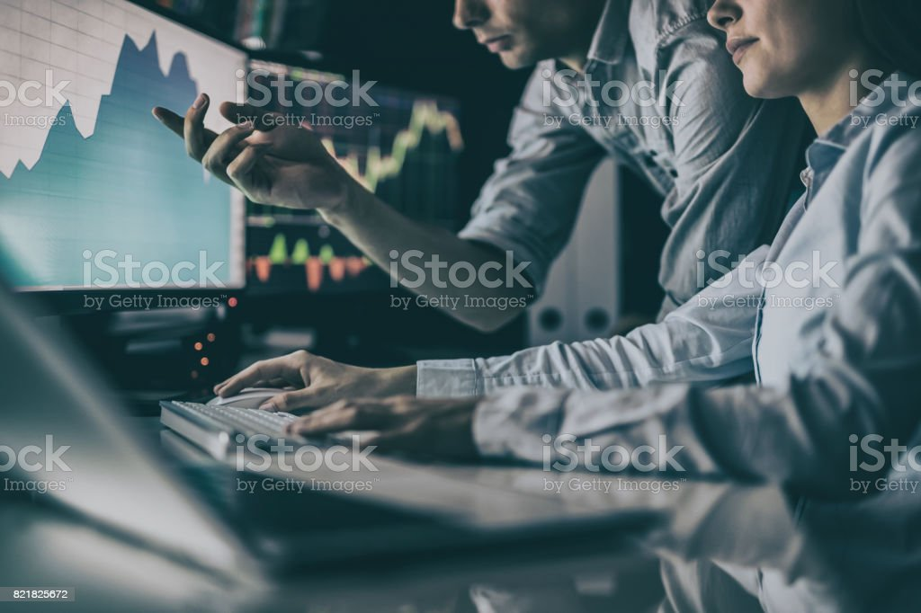 Analyzing graphs and reports for investment purposes. Creative teamwork traders. stock photo