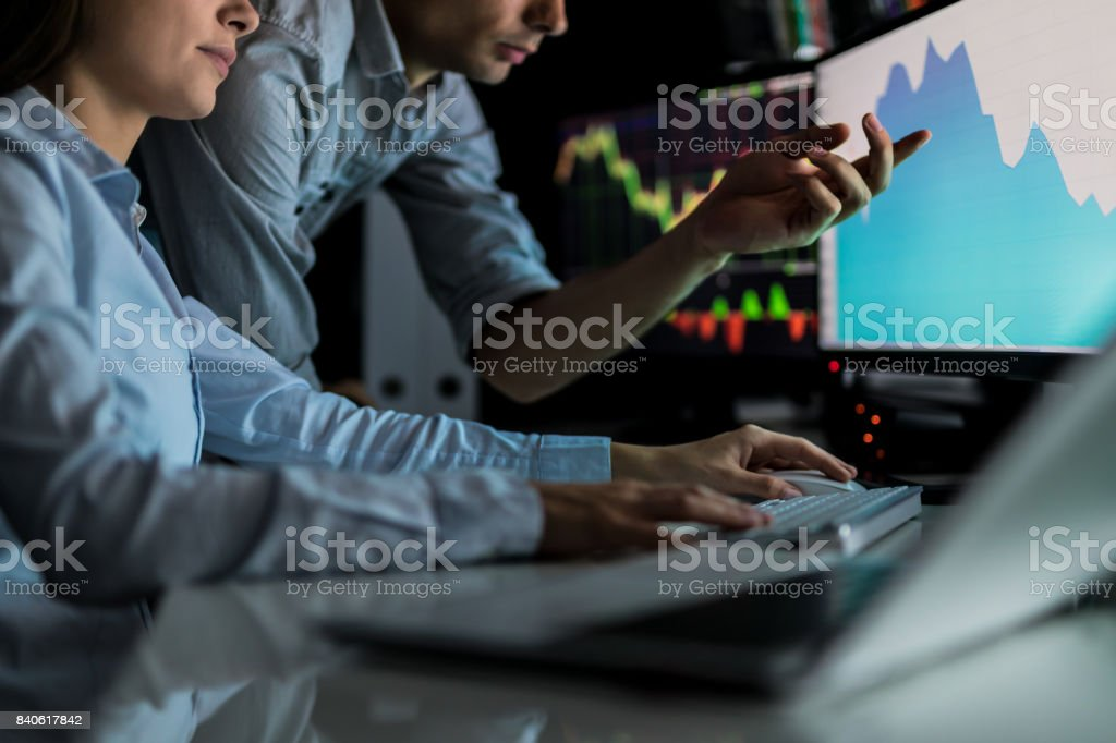 Analyzing graphs and reports for investment purposes. Creative teamwork traders. – zdjęcie