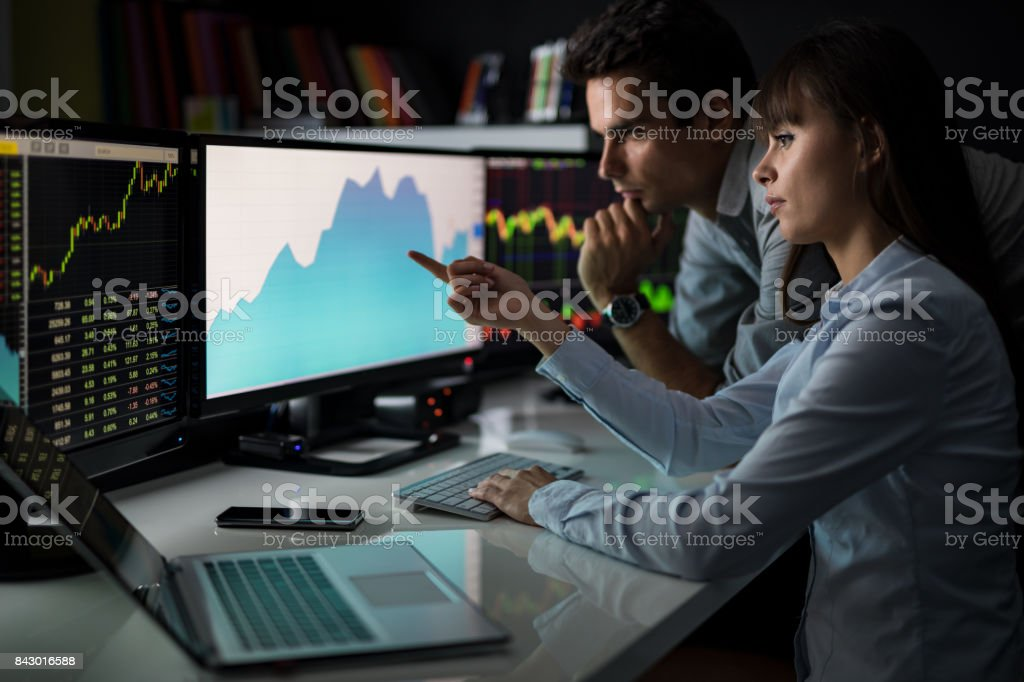 Analyzing graphs and reports for investment purposes. Creative teamwork traders. - foto stock