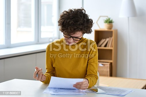 Serious concentrated young woman in glasses sitting at table and analyzing tax documents in home office