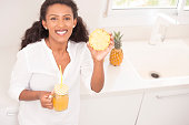 Young attractive woman showing a slice of sweet fresh pineapple. Woman enjoying to eat fruit and drink pineapple juice. Woman standing at the kitchen, leaning on the countertop, looking at camera with a friendly smile.