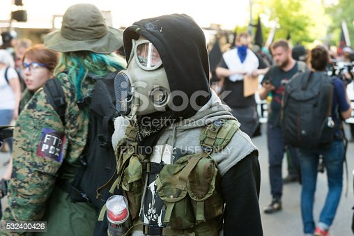Seattle, USA - May 1, 2016: Masked Anarchists wearing gas masks late in the day during the Anti Capitalist Protest in downtown on 4th avenue.