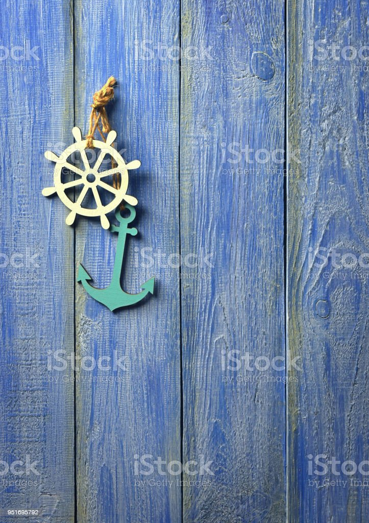 Anchor and helm on a blue wooden background. The concept of sea travel. Summer vacation at the sea. Marine themes. Close-up. stock photo