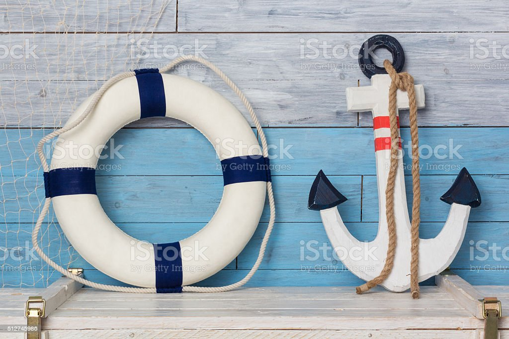 Anchor and life buoy on wood background blue-white stock photo