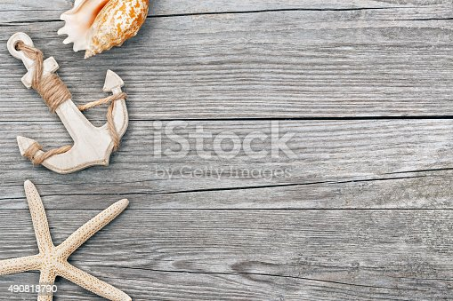 istock anchor and seashells on wooden background 490818790