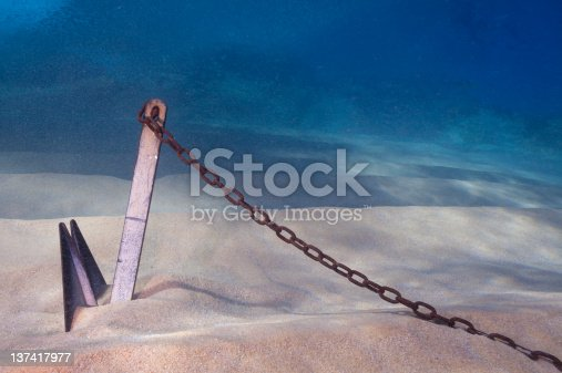 Large metal anchor buried in a sandy bottom underwater.