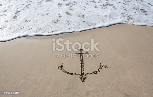istock Anchor drawn in the sand on the beach 622439932