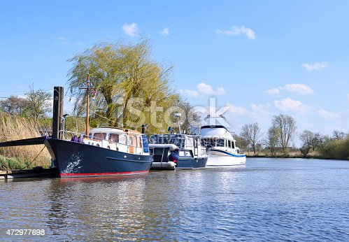 Anchored sailing ship and motorboats at a river. Sunny day at the river in Northern Germany.