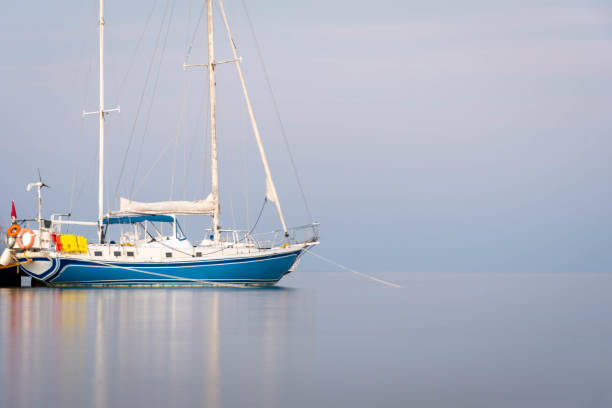 Anchored Caribbean sailboat at dusk on isolated simple background.