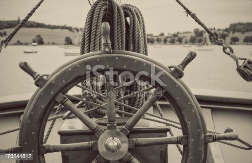 A close look at the helm of a tall ship morred in a still harbour.  Toned black and white image.