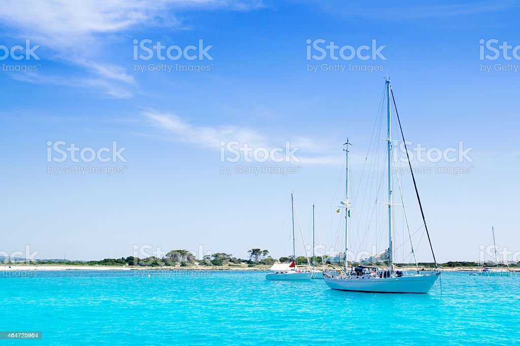 anchored sailboats in turquoise Formentera beach stock photo