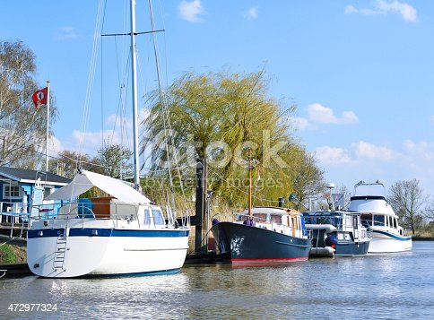 Anchored boats. Sailing ship and motorboats moored at a pier at a riverside. Sunny day at the river in Northern Germany. Nautical vessel.