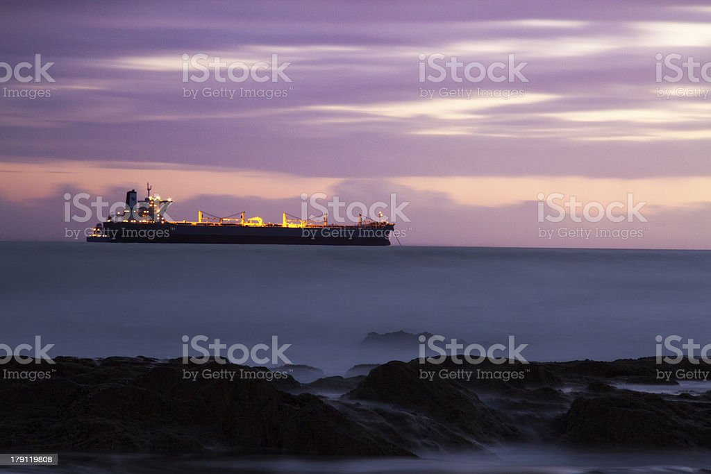 Anchored ship and purple sunset clouds stock photo