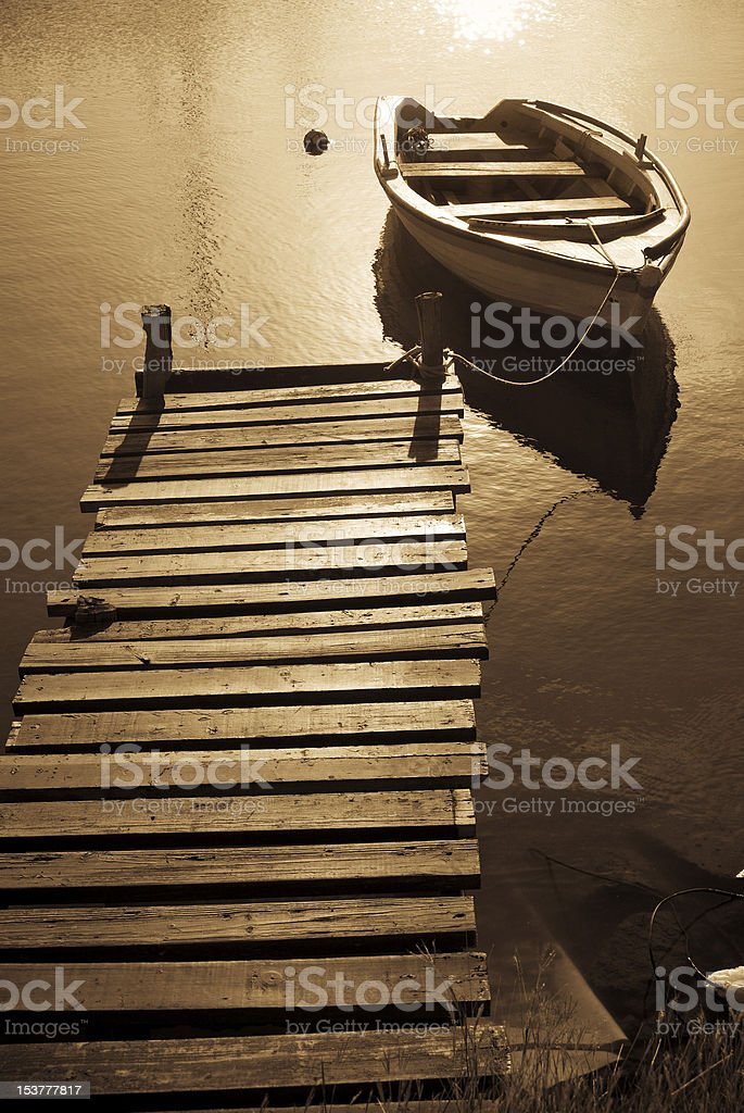 anchored small boat at sunset royalty-free stock photo