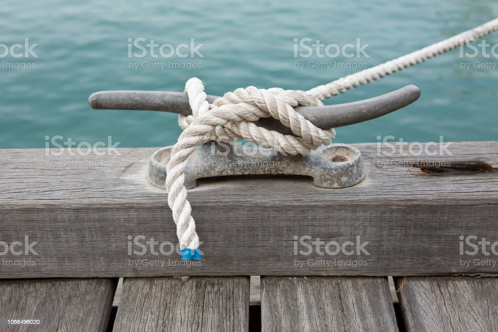 Anchored white rope on dock by water stock photo