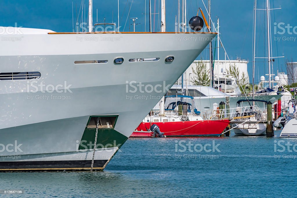 Anchored yacht's bow with marina and red sailboat in background stock photo
