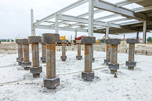 Anchor's nuts on screw are peaking from concrete in building. Close up the anchor bolts in concrete base of new edifice with reinforcement at building site. cusp stock pictures, royalty-free photos & images