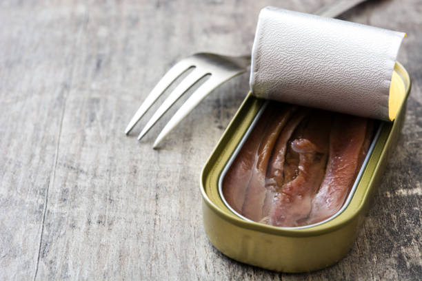 Anchovies can Anchovies can on wooden background anchovy stock pictures, royalty-free photos & images