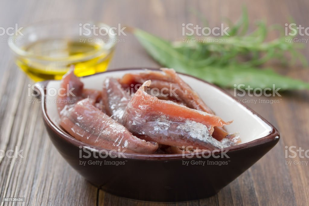 anchovies in dish with oil and herbs on brown wooden background stock photo
