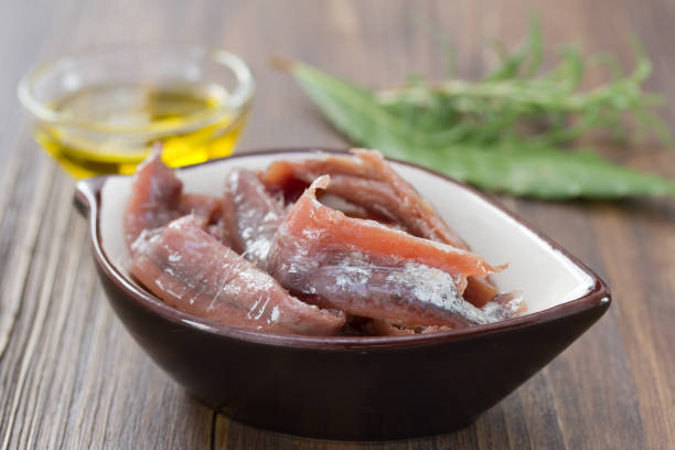anchovies in dish with oil and herbs on brown wooden background anchovies in dish with oil and herbs on brown wooden background anchovy stock pictures, royalty-free photos & images