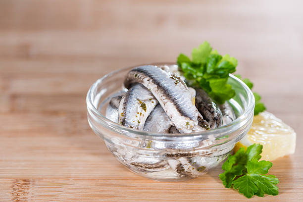 Anchovis Pickled Anchovis with herbs (close-up shot) on wooden background anchovy stock pictures, royalty-free photos & images