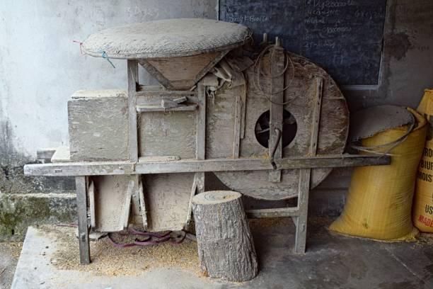 Ancienne écorceuse de riz Le riz récolté est nettoyé de ces impuretés en aspirant les brins d'herbe et la terre et en éliminant les pierres. Le rizon passe dans l'écorceuse, une machine, composée de deux rouleaux, crée exprès pour séparer l'écosse (balle) du riz. On obtient le riz en paille (riz complet). Afin d'obtenir le riz blanc, il faut le blanchir en faisant passer le riz complet entre deux pierres. riz stock pictures, royalty-free photos & images