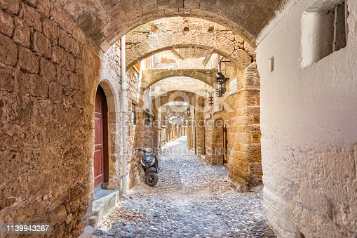 A scooter is parked in an ancient alley with row of homes in old town Rhodes, Greece.