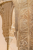 Ancient caligraphy detail in a column. Alhambra palace, Granada, Andalusia, Spain.