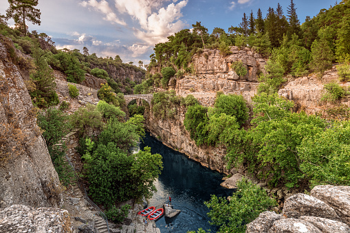 Ancient arch bridge over the Koprucay river gorge in Koprulu national Park in Turkey. Panoramic scenic view of the canyon and blue stormy mountain river