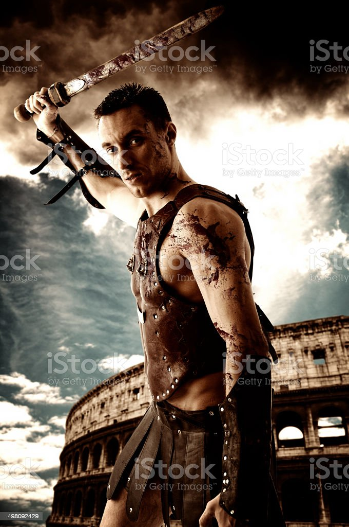 Ancient armed gladiator soldier in battle pose on coliseum background stock photo