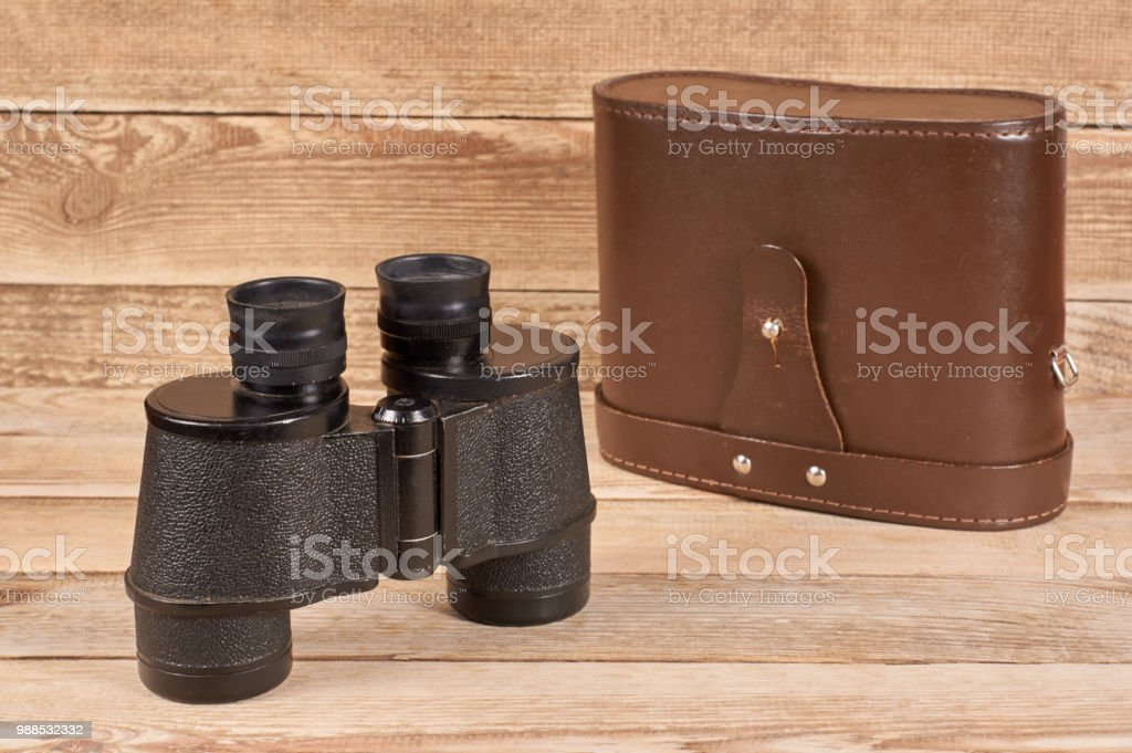 Ancient army binoculars with a case on a wooden background stock photo