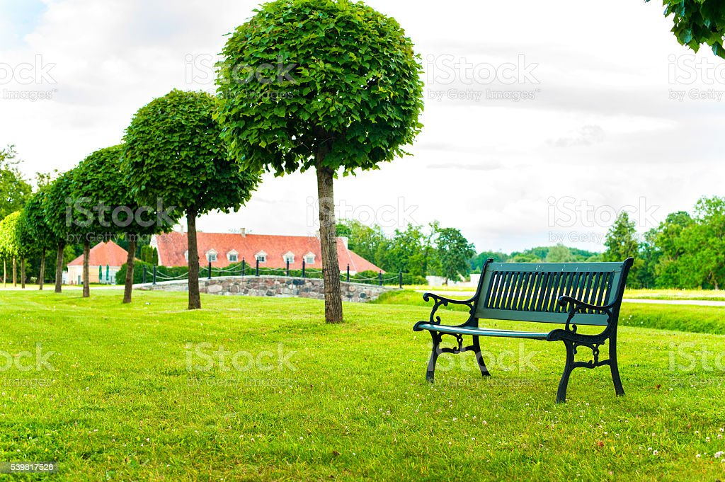 Ancient bench in green garden of Rundale in Latvia. Outdoors. stock photo