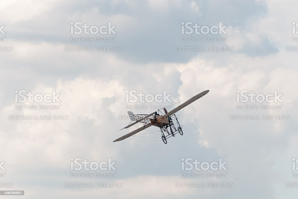 Ancient Blériot XI Gnome aircraft flies against cloudy sky background royalty-free stock photo
