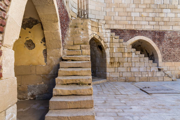 Ancient brick building with two shabby stone stairways and two crumbling arched alcoves on street stock photo
